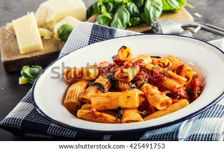 Pasta. Italian and Mediterrannean cuisine. Pasta Rigatoni with tomato sauce basil leaves garlic and parmesan cheese. An old home kitchen with old kitchen utensils. - stock photo