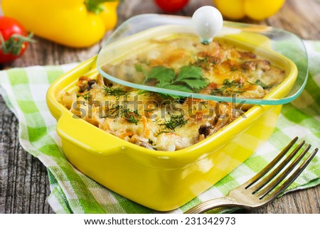 pasta, mushrooms and cheese gratin in casserole dish - stock photo