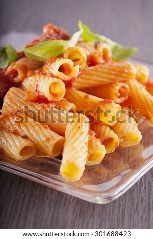 Pasta over glass plate, with tomato and basil, vertical image - stock photo