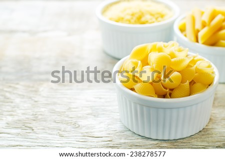 pasta Penne in a white bowl on white wood background. tinting. selective focus - stock photo
