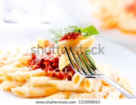 Pasta. Penne Pasta with Bolognese Sauce, Parmesan Cheese and Basil on a Fork. Italian Cuisine. Mediterranean food - stock photo
