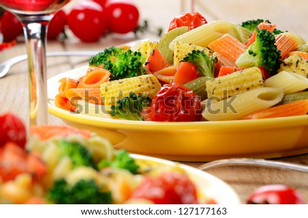 Pasta penne salad with broccoli, carrot, corn, served with red wine - stock photo