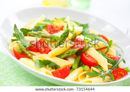 Pasta penne with asparagus,tomato and rucola in bowl - stock photo