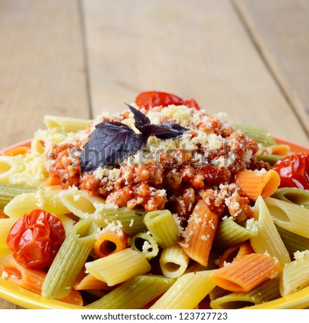Pasta penne with bolognese tomato beef sauce on the kitchen table - stock photo
