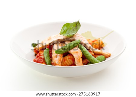 Pasta Penne with Fried Salmon. Garnished with Tomato Sauce - stock photo