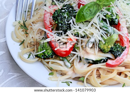 Pasta Primavera made with fresh broccoli, asparagus, red bell pepper and zucchini and served with freshly grated parmesan cheese. - stock photo