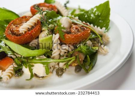 Pasta salad with avocado tomato rocket  - stock photo