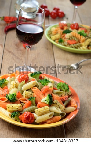 Pasta salad with broccoli carrot corn served with red wine - stock photo
