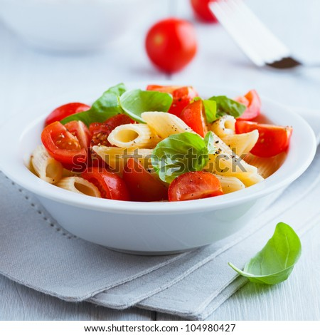 Pasta salad with cherry tomatoes and basil - stock photo