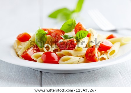 Pasta salad with cherry tomatoes and basil leaves - stock photo