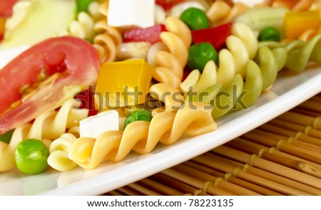 Pasta salad with fresh vegetables (tomato, pea, bell pepper) and cheese (Selective Focus, Focus on the first pasta) - stock photo