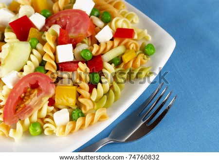 Pasta salad with fresh vegetables (tomato, pea, bell pepper, cucumber) and cheese on plate with fork next to it on blue cotton place mat (Selective Focus, Focus on the front of the salad) - stock photo