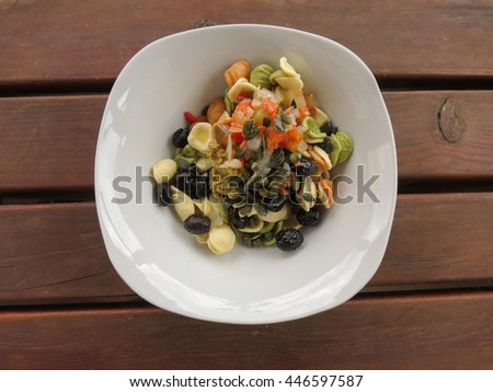 Pasta salad with three colour orecchiette, baked black olives, mixed pickle, olive tapenade, pumpkin seeds - stock photo