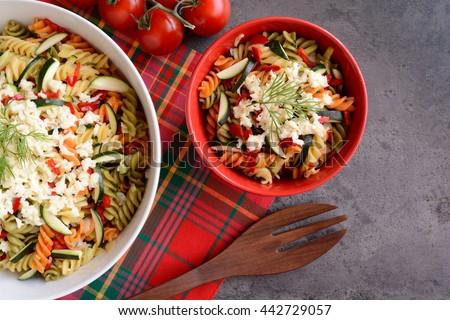 Pasta salad with zucchini, onion, garlic, chili and mozzarella - stock photo