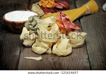 Pasta spaghetti, fettuccine pasta, whole flour in wooden bow on a wood background - stock photo