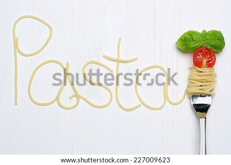 Pasta spaghetti noodles on a fork with tomato and basil - stock photo