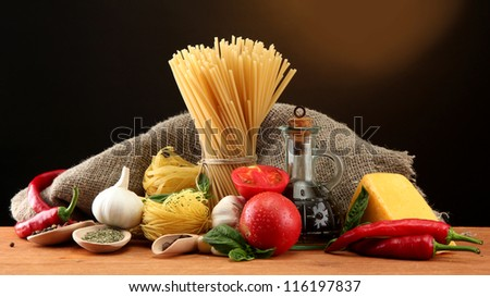 Pasta spaghetti, vegetables and spices, on wooden table, on brown background - stock photo