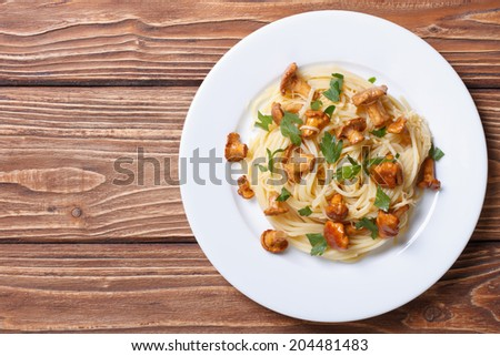 Pasta spaghetti with chanterelles mushrooms on a wooden background top view  - stock photo