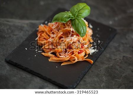 Pasta tagiatelle with tomato on black woodboard - stock photo