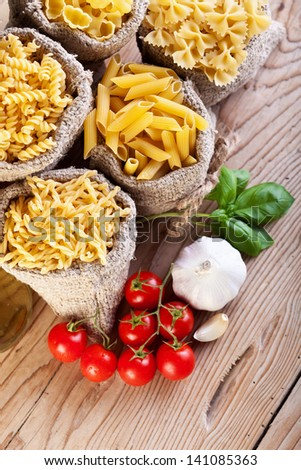 Pasta variety in small bags and specific cooking ingredients - top view - stock photo
