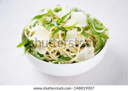 Pasta with arugula (rocket) and parmesan - stock photo