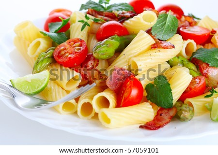 Pasta with asparagus, tomatoes and bacon - stock photo