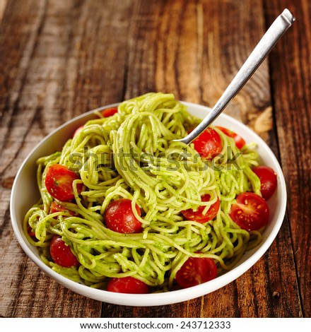 Pasta with avocado sauce and cherry tomatoes - stock photo