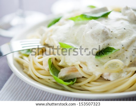 Pasta with chicken, creamy sauce and basil - stock photo