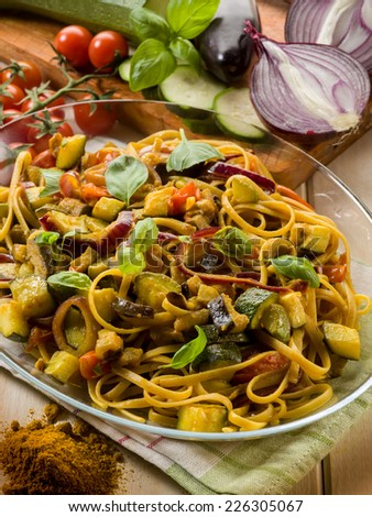 pasta with eggplants zucchinis tomatoes and curry - stock photo
