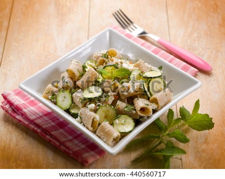pasta with feta cheese zucchinis and mint leaf, selective focus - stock photo