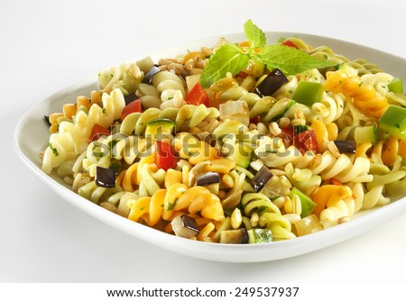 Pasta with fresh vegetables on white plate - stock photo
