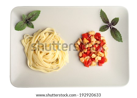 Pasta with grilled chicken, basil and peppers in a plate isolated - stock photo
