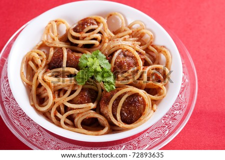Pasta with meatballs and tomato sauce on red background - stock photo