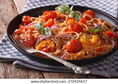 Pasta with minced meat and vegetables close up in a black plate. Horizontal  - stock photo