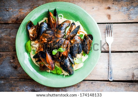 Pasta with mussels and basil - stock photo