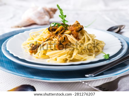Pasta with mussels with tomatoes and arugula. - stock photo