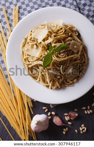 pasta with pesto, pine nuts and parmesan cheese on a plate and ingredients on the table close-up. vertical top view - stock photo