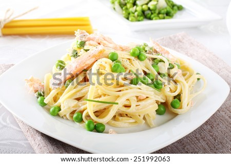 Pasta with salmon and peas on complex background - stock photo