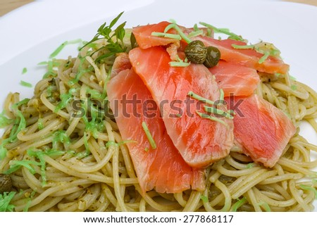 Pasta with salmon, green pesto cheese and capers - stock photo