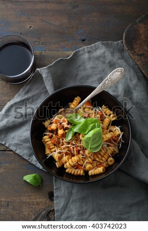 pasta with sauce in bowl on rustic table - stock photo