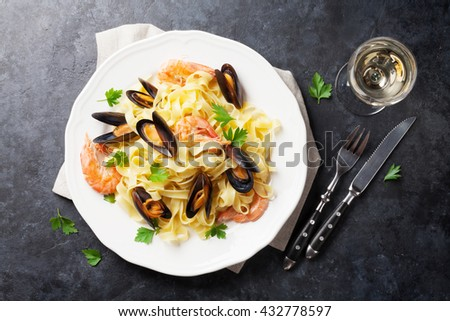 Pasta with seafood and white wine on stone table. Mussels and prawns. Top view - stock photo