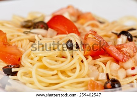 Pasta with tomato, black olives, capers and greens - stock photo