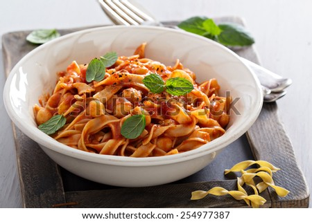 Pasta with tomato sauce, chickpeas and cardamom - stock photo