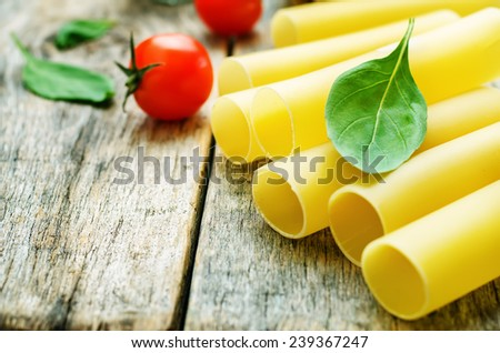 pasta with tomatoes and Basil on a dark wood background. tinting. selective focus - stock photo