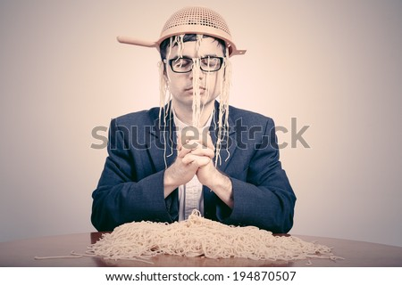 Pastafarian wearing a colander praying for pasta to the Flying Spaghetti Monster. - stock photo