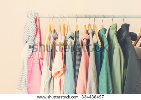 Pastel Color Female Clothes in a Row on Open Hanger. Toned image - stock photo