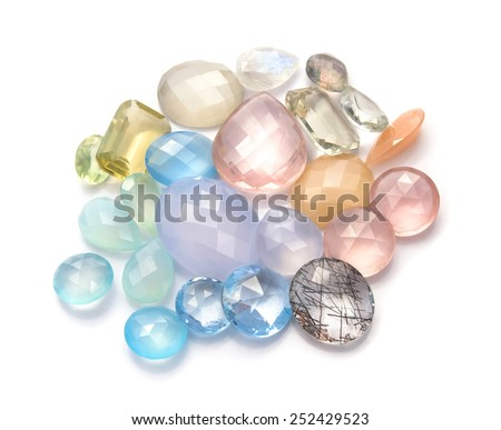 Pastel color gemstones collection on the white background. Beautiful real gems: rose quartz, peach moonstone, chalcedony, fluorite, topaz blue sky, rainbow moonstone, green amethyst and more. - stock photo