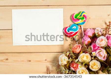 Pastel color roses flowers and empty tag for your text with heart shape candy on wooden background - stock photo