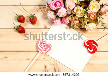 Pastel color tone  roses flowers and empty tag for your text with heart shape candy on wooden background - stock photo