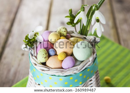 Pastel colored easter eggs in white wicker basket decorated with polka dot ribbon and spring flowers on green striped cloth over grunge style wooden table - stock photo